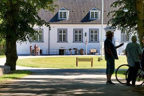 Hvidt hus med mennesker foran under træer
