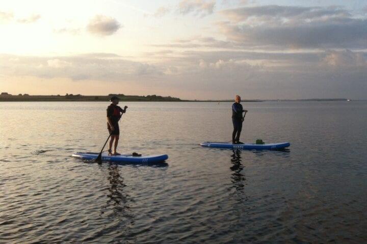 To personer står op på paddle boards