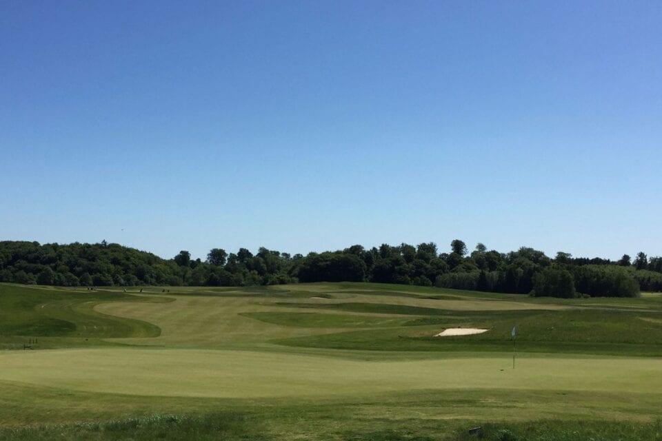 Golfbane med blå himmel